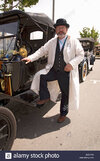 driver-in-driving-clothes-posing-in-front-of-antique-car-in-santa-BGGYA8.jpg